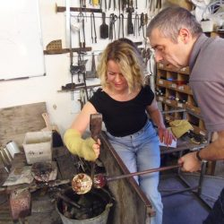 A Glassmaker Helping a Visitor
